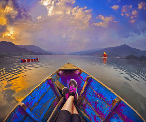 Feet luing in the boat ,landscape with  Himalaya mountains and clouds,Pokhara, Nepal
