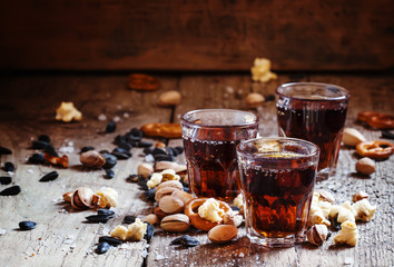Cola glasses, sweet and savory snacks, old wooden table, unhealt
