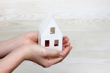 paper model of a new house in human hands