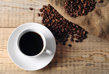 Cup with coffee beans on wooden table