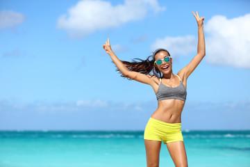 Happy fit girl wearing wayfarer mirror sunglasses on beach in