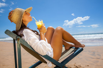 Young woman lying on the beach and refreshing with juice