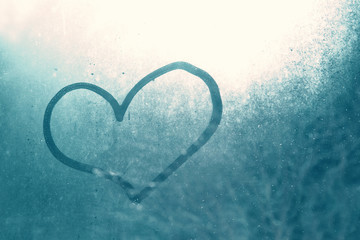 Love heart shape hand drawn on wet, frozen window pane with blue sunlight background. Selective focus used.