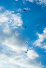 Five aircraft formation flying in the sky among the clouds