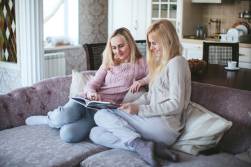 Two girls look a photo album on the sofa
