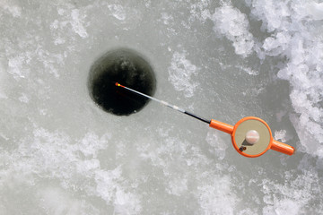 Fishing by a winter plastic rod in the ice hole on the pond