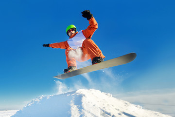 Snowboarder jumping blue sky in background