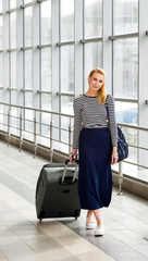 young blonde woman talking on the station with a suitcase and a backpack. gathered on a trip