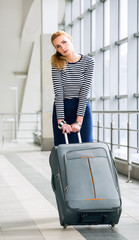 young blonde woman pulling heavy suitcase on the station was going on a trip. It is difficult to carry luggage. Tired