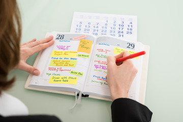 Fototapete - Businesswoman With Calendar Writing Schedule In Diary