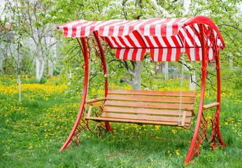 Swing bench near children house in garden.