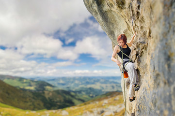 Portrait of young female rock climber on steep overhanging rock cliff. Holding the rope and looking down. Beautiful blue sky and mountains on the background.