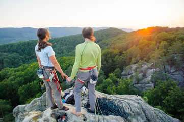 Young couple of climbers standing on the mountain peak holding hands and enjoying beautiful nature view at sunset after challenging climb. Climbing equipment.
