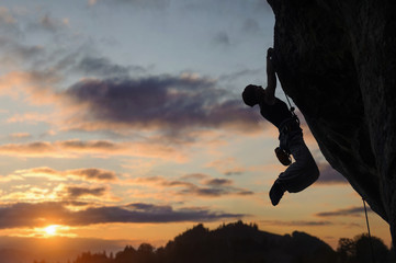 Silhouette of athletic woman rock climber climbing steep rock wall against amazing sunset sky in the mountains. Girl is hanging on two hands.