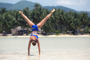Handstand yoga pose by woman on the beach near the sea in island of Thailand