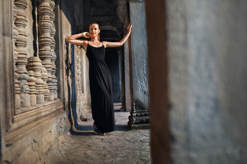 Cambodia Tourist Attraction. Happy Beautiful Religious Young Woman Relaxing In Corridor At Prasat Angkor Khmer Wat Temple, Siem Reap. Famous Landmark, Travel Destination. Harmony, Tranquility Concept