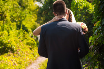 Bride holds groom. Back view