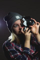 Portrait of hipster girl taking picture with retro camera