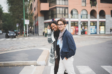 beautiful multiethnic couple walking outdoor in the city, hand i