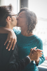 Half length of a multiethnic couple of lover kissing and hugging