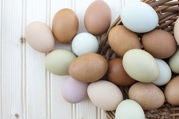 Fresh organic chickeneggs overflow out of basket on wooden backg