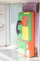 Old public telephone with rust.