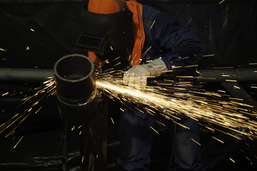 The worker grinding metal in manufacturing plant, sparks flying