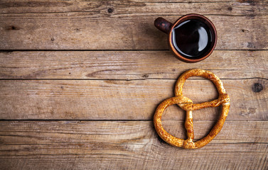 Delicious Breakfast, a pretzel with coffee on wooden background.