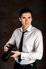 Professional photographer ready for shot in studio in white shirt and black tie