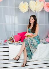 Pretty girl in colored decor studio.
