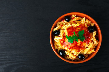 fusilli pasta and olives with parsley and ketchup in a bowl on a wooden black background