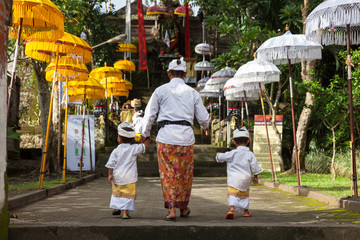 Man with children walks up the stairs during the celebration before Nyepi (Balinese Day of Silence). Ubud, Indonesia.