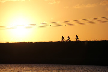 sporty company friends on bicycles outdoors against sunset.