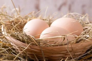 Three hen eggs in straw nest