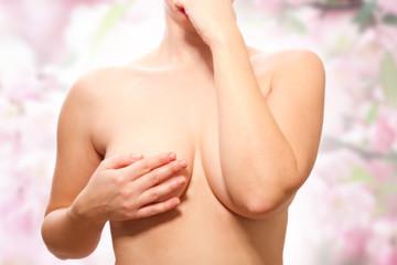 nackte Frau bedeckt ihre Brust -Frontal mit Hintergrund
