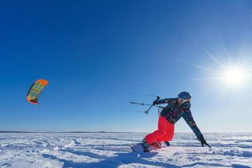 The sportsman on a snowboard runs kite