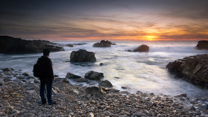 Contemplating the sunset on a isolated beach, pebble landscape