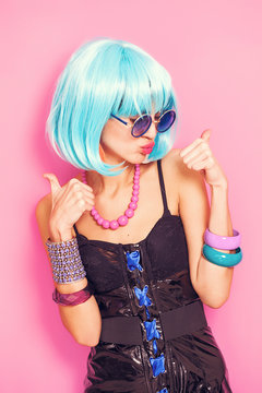 Cool pop girl portrait with thumbs up wearing blue wig