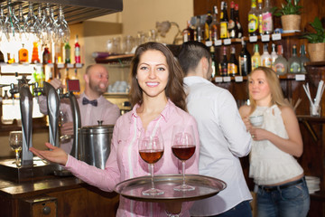 Waitress holding tray with glasses