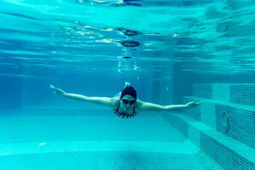 girl swimmimg underwater in pool