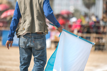 Male hand holding a white flag.