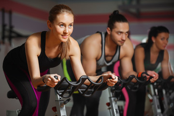 Group of fit people cycling in fitness club