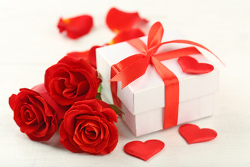 Gift box, rose flowers and decorative hearts on light wooden background