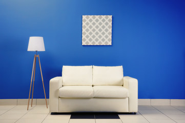 Comfortable white sofa on blue wall background