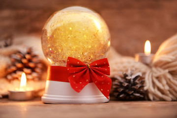 Christmas snow globe with ribbon bow in candlelight on wooden table closeup