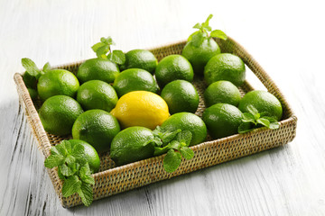 Wicker basket of limes and one lemon on table