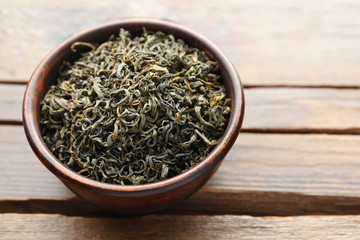 Green tea in a round bowl on wooden table, close up