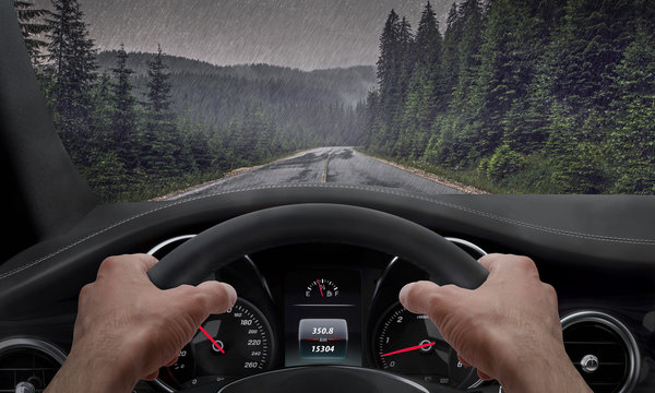 Driving in rainy weather. View from the driver angle while hands on the wheel. Rain splashed windshield.