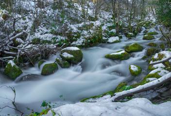 snowy river with mossy rocks