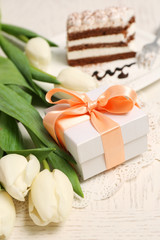 Sweet creamy cake with flowers and present box on wooden table closeup